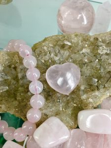 A rose quartz bracelet with a rose quartz heart laying on top of cluster of lithium quartz