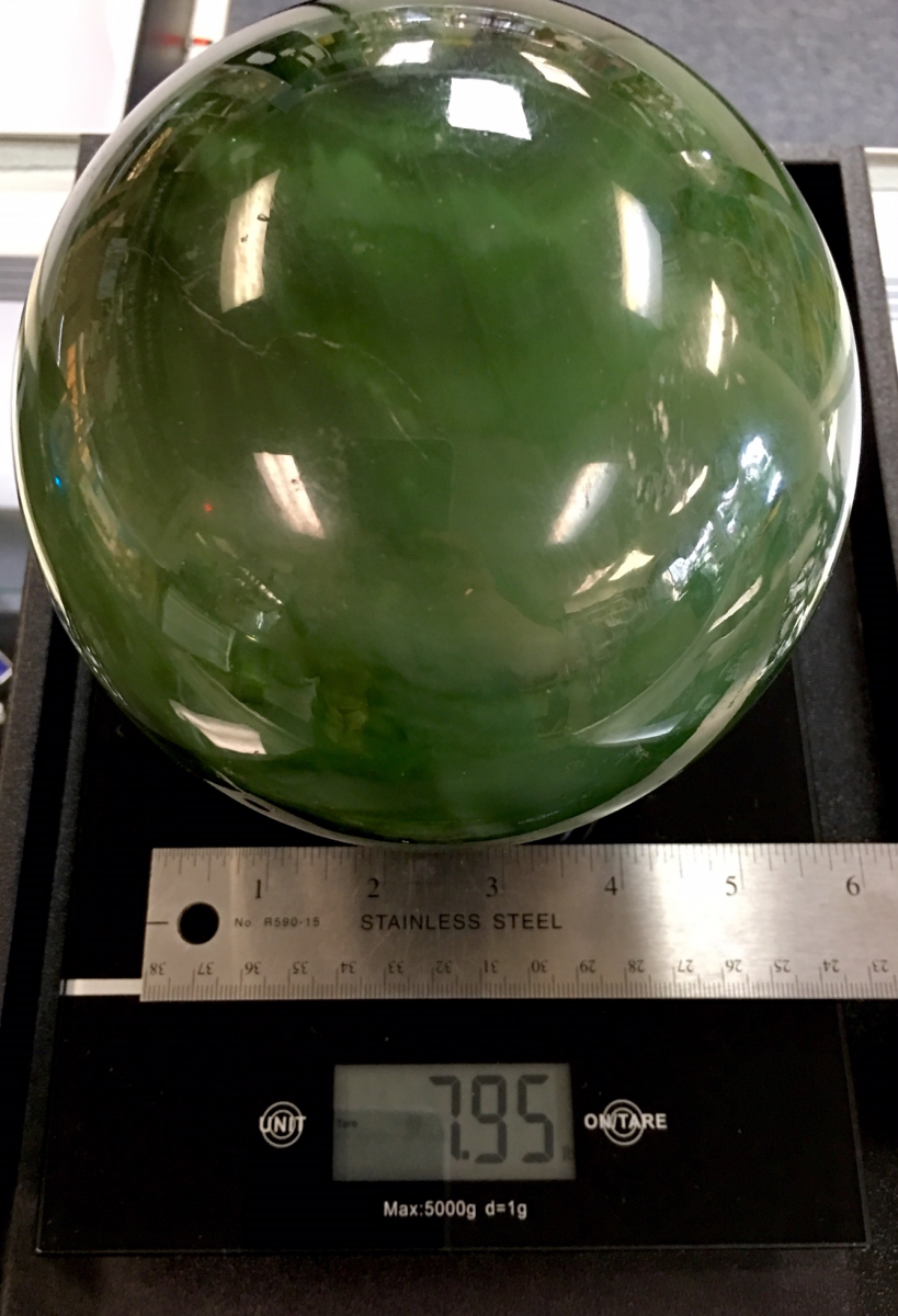 A 5.5 inch chatoyant (reflective) jade sphere weighing almost 8 pounds. Shown on a digital scale with a ruler.