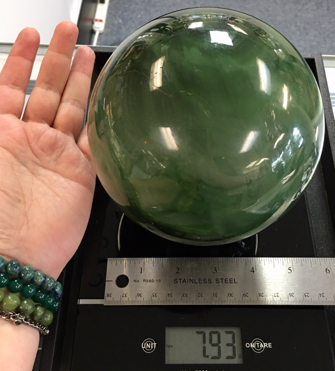 a comparison photo of the almost 8 pound chatoyant jade sphere next to Melina's hand for size. Shown on a digital scale with a ruler.