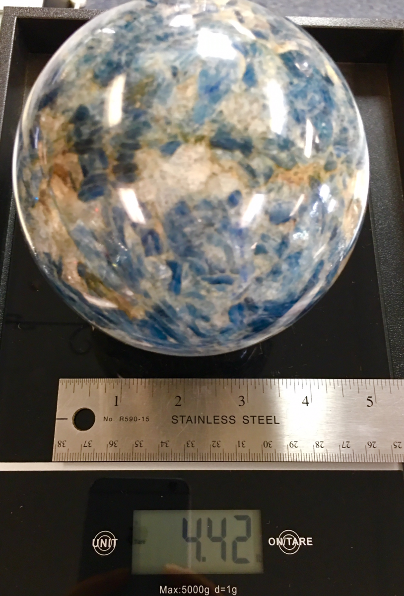 a blue kyanite sphere about 4 inches in diameter weighing almost 4 and a half pounds. shown on a digital scale with ruler for size