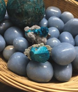 Cavansite laying on top of smooth tumbled angelite with a large apatite sphere